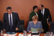German Chancellor Angela Merkel reads a document as other members of her government stand nearby at the first government cabinet meeting since the collapse of talks over a new government coalition on November 22, 2017 in Berlin, Germany. While the previous German government is still functoning as normal, the creation of a new government following federal elections last September is in limbo after the collapse of coalition talks last Sunday between the Christian Democrats (CDU/CSU), the Free Democrats (FDP) and the Greens Party (Buendnis 90/Die Gruenen). Currently the most likely course is new elections in coming months.
