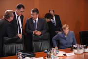 German Chancellor Angela Merkel (R) sits down as other members of her government stand nearby at the first government cabinet meeting since the collapse of talks over a new government coalition on November 22, 2017 in Berlin, Germany. While the previous German government is still functoning as normal, the creation of a new government following federal elections last September is in limbo after the collapse of coalition talks last Sunday between the Christian Democrats (CDU/CSU), the Free Democrats (FDP) and the Greens Party (Buendnis 90/Die Gruenen). Currently the most likely course is new elections in coming months.