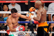(R-L) Floyd Mayweather Jr. knocks out Victor Ortiz in the fourth round during their WBC welterweight title fight at the MGM Grand Garden Arena on September 17, 2011 in Las Vegas, Nevada.