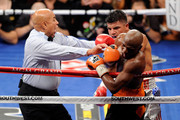 Referee Joe Cortez pulls Victor Ortiz off Floyd Mayweather Jr. as Ortiz is called for a head-butt in the fourth round during their WBC welterweight title fight at the MGM Grand Garden Arena on September 17, 2011 in Las Vegas, Nevada.