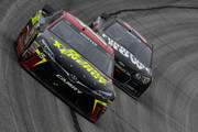 Clint Bowyer, driver of the #15 5-hour ENERGY Toyota, leads Martin Truex Jr., driver of the #78 Furniture Row Chevrolet, during the NASCAR Sprint Cup Series Folds of Honor QuikTrip 500 at Atlanta Motor Speedway on March 1, 2015 in Hampton, Georgia.