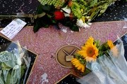 A picture taken  on September 28, 2017 shows flowers placed by fans on the Hollywood Walk of Fame star belonging to Playboy Magazine founder Hugh Hefner, who died at the age of 91, in Hollywood, California.  / AFP PHOTO / Mark RALSTON