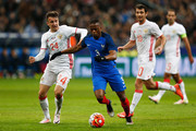 Patrice Evra of France battles for the ball with Aleksandr Golovin and Alan Dzagoev of Russia during the International Friendly match between France and Russia held at Stade de France on March 29, 2016 in Paris, France.