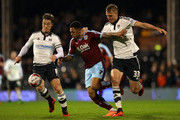 Andre Gray of Burnley is tackled by Scott Parker and Dan Burn of Fulham during the Sky Bet Championship match between Fulham and Burnley at Craven Cottage on March 8, 2016 in London, United Kingdom.