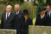 """CHATSWORTH, ENGLAND, OCTOBER 2: Prince Charles, the Prince of Wales, and Camilla Duchess of Cornwall (R) follow the The Duke and Duchess of Devonshire (C) as the coffin of Deborah, Dowager Duchess of Devonshire arrives at St Peter's Church, Edensor, on October 2, 2014 in Chatsworth, England, ahead of her funeral. Deborah Cavendish, Dowager Duchess Of Devonshire, the last surviving Mitford sister, died aged 94 on September 24, 2014. Deborah was known as the """"housewife duchess"""", and her noted business acumen made Chatsworth House one of the most successful and profitable stately homes in England."""