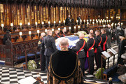 Queen Elizabeth II (left) watches as pall bearers carry the coffin of the Duke of Edinburgh during his funeral in St George's Chapel at Windsor Castle on April 17, 2021 in Windsor, England. Prince Philip of Greece and Denmark was born 10 June 1921, in Greece. He served in the British Royal Navy and fought in WWII. He married the then Princess Elizabeth on 20 November 1947 and was created Duke of Edinburgh, Earl of Merioneth, and Baron Greenwich by King VI. He served as Prince Consort to Queen Elizabeth II until his death on April 9 2021, months short of his 100th birthday. His funeral takes place today at Windsor Castle with only 30 guests invited due to Coronavirus pandemic restrictions.