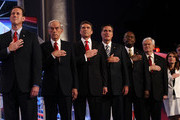 Republican presidential candidates (L-R) Rick Santorum, Rep. Ron Paul (R-TX), Texas Gov. Rick Perry, Mitt Romney, Herman Cain, Newt Gingrich, Rep. Michele Bachmann (R-MN), and Jon Huntsman place their hands over their hearts during the national anthem prior to a debate at Constitution Hall November 22, 2011 in Washington, DC. The debate, hosted by CNN and in partnership with the Heritage Foundation and the American Enterprise Institute, was expected to focus primarily on national security, foreign policy and the economy.