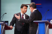Rebulican presidential candidates (L-R) Louisiana Gov. Bobby Jindal and Rick Perry chat during a break in a presidential forum hosted by FOX News and Facebook at the Quicken Loans Arena August 6, 2015 in Cleveland, OH. Seven GOP candidates were selected to participate in the forum based on their rank in an average of the five most recent national political polls. The top ten polling Republican candidates will participate in a debate following the forum.