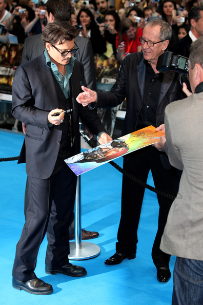 Geoffrey Rush Actors Johnny Depp and Geoffrey Rush sign autographs for the fans during the UK Film Premiere of Pirates of the Carribean 4: On Stranger Tides at Vue Westfield on May 12, 2011 in London, England.