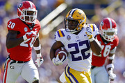 Clyde Edwards-Helaire #22 of the LSU Tigers runs with the ball as J.R. Reed #20 of the Georgia Bulldogs defends during the first half at Tiger Stadium on October 13, 2018 in Baton Rouge, Louisiana.