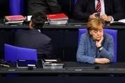 TOPSHOT - German Chancellor Angela Merkel and German Vice Chancellor and Foreign Minister Sigmar Gabriel take their seats to attend a plenary session at the Bundestag, on December 12, 2017 in Berlin.  / AFP PHOTO / John MACDOUGALL