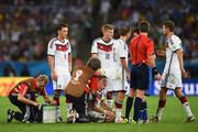 Bastian Schweinsteiger of Germany receives treatment as teammates Mesut Oezil, Toni Kroos, Philipp Lahm and Thomas Mueller look on during the 2014 FIFA World Cup Brazil Final match between Germany and Argentina at Maracana on July 13, 2014 in Rio de Janeiro, Brazil.
