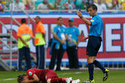 Fabio Coentrao of Portugal lies on the field after an injury as referee Milorad Mazic signals for a trainer during the 2014 FIFA World Cup Brazil Group G match between Germany and Portugal at Arena Fonte Nova on June 16, 2014 in Salvador, Brazil.