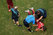 An injured Fabio Coentrao of Portugal lies on the pitch as referee Milorad Mazic stands over during the 2014 FIFA World Cup Brazil Group G match between Germany and Portugal at Arena Fonte Nova on June 16, 2014 in Salvador, Brazil.