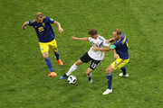 Thomas Mueller of Germany is tackled by Ola Toivonen (l) and Andreas Granqvist of Sweden during the 2018 FIFA World Cup Russia group F match between Germany and Sweden at Fisht Stadium on June 23, 2018 in Sochi, Russia.
