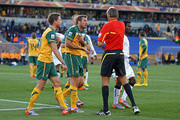Harry Kewell (L) of Australia explains the ball hit his chest and Lucas Neill pleads with the referee as Roberto Rosetti sends off Kewell for handball and awards Ghana a penalty during the 2010 FIFA World Cup South Africa Group D match between Ghana and Australia at the Royal Bafokeng Stadium on June 19, 2010 in Rustenburg, South Africa.