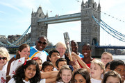 (EDITORIAL USE ONLY, NO SALES)  In this handout image provided by Glasgow 2014 Ltd, (L-R) Michael Pusey, Mayor of London Boris Johnson, Faramolu Johnson and Olympic gold medalist Christine Ohurugu with children from Albert Salter primary school pose with Queen's Baton as it arrives in London on June 06, 2014 in London, England. England is nation 69 of 70 nations and territories the Queen's Baton will visit.