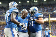 Reggie Bush #21 of the Detroit Lions celebrates with teammates Cornelius Lucas #77 and Dominic Raiola #51 after scoring on a 21 yard touchdown during the fourth quarter of the game against the Bay Packers at Ford Field on September 21, 2014 in Detroit, Michigan.