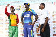In this handout image provided by CPL T20, Shoaib Malik (L) of Guyana Amazon Warriors toss the coin as Jason Holder (C) of Barbados Tridents and match referee Denavon Hayles (R)  look on during match 6 of the Hero Caribbean Premier League match between Guyana Amazon Warriors and Barbados Tridents at Guyana National Stadium on August 12, 2018 in Providence, Guyana.