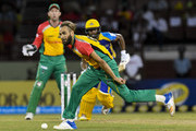 In this handout image provided by CPL T20, Imran Tahir (L) of Guyana Amazon Warriors attempts to stop Shai Hope (R) of Barbados Tridents during match 6 of the Hero Caribbean Premier League match between Guyana Amazon Warriors and Barbados Tridents at Guyana National Stadium on August 12, 2018 in Providence, Guyana.