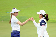 Paula Creamer of the United States bumps fists with Inbee Park of South Korea on the 18th hole during the first round of the HSBC Women's Champions at Sentosa Golf Club on March 3, 2016 in Singapore, Singapore.