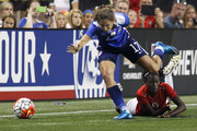 Tobin Heath #17 of the United States trips over Nerilia Mondesir #9 of Haiti while chasing the ball during the first half of the U.S. Women's 2015 World Cup victory tour match at Ford Field on September 17, 2015, in Detroit, Michigan.