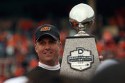 Head coach Mike Gundy of the Oklahoma State Cowboys carries the Heart of Dallas Bowl trophy after a 58-14 win against the Purdue Boilermakers during the Heart of Dallas Bowl at Cotton Bowl on January 1, 2013 in Dallas, Texas.