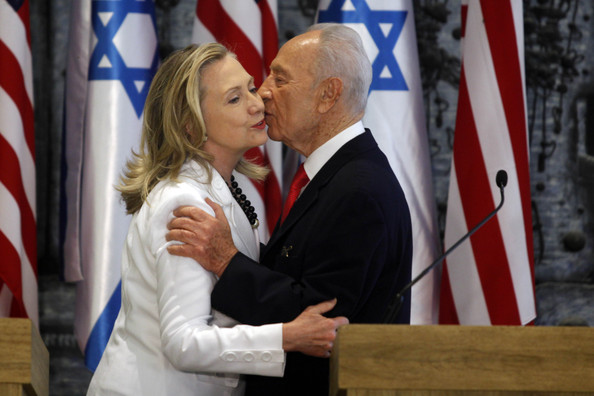 Hillary Clinton (ISRAEL OUT) Israeli President Shimon Peres (R) and US Secretary of State Hillary Clinton kiss after a joint press conference on July 16, 2012 in Jerusalem, Israel. Clinton is in Israel to discuss diplomacy with Iran, Syria and Egypt in addition to peace talks regarding the Middle East.