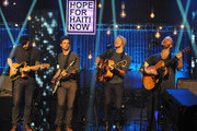 In this handout photo provided by MTV, (L-R) Jonny Buckland, Guy Berryman, Chris Martin and Will Champion of Coldplay perform on stage at the Hope For Haiti Now concert, a global benefit for earthquake relief, at The Hospital Club on January 22, 2010 in London, England.