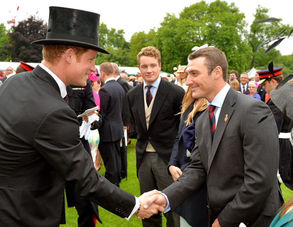 Prince Harry (L) talks to Corporal of Horse Chris Nicol of the Household Cavalry during a special Garden Party for the Regiment at Buckingham Palace on May 28, 2014 in London, Untied Kingdom.