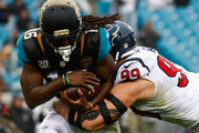 Denard Robinson #16 of the Jacksonville Jaguars is tackled by  J.J. Watt #99 of the Houston Texans during the game at EverBank Field on December 7, 2014 in Jacksonville, Florida.