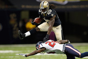 Chris Ivory #29 of the New Orleans Saints jumps over  Johnathan Joseph #24 of the Houston Texans at the Mercedes-Benz Superdome on August 25, 2012 in New Orleans, Louisiana.