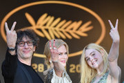 (From L) British novelist Neil Gaiman, Australian actress Nicole Kidman and US actress Elle Fanning gesture as they arrive on May 21, 2017 for the screening of the film 'How to talk to Girls at Parties' at the 70th edition of the Cannes Film Festival in Cannes, southern France.  / AFP PHOTO / Alberto PIZZOLI