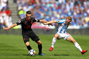 Aaron Ramsey of Arsenal battles for possession with Alex Pritchard of Huddersfield Town during the Premier League match between Huddersfield Town and Arsenal at John Smith's Stadium on May 13, 2018 in Huddersfield, England.