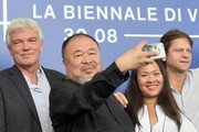 """Chinese artist and producer Ai Weiwei (C) attends the photocall of the movie """"Human Flow"""" presented in competition at the 74th Venice Film Festival on September 1, 2017 at Venice Lido.  / AFP PHOTO / Tiziana FABI"""
