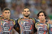 (L-R) Justin Hodges, Greg Inglis and Johnathan Thurston of the Indigenous All Stars embrace for the national anthem before the NRL pre-season match between the Indigenous All Stars and the NRL All Stars at Cbus Super Stadium on February 13, 2015 in Gold Coast, Australia.