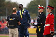 Bronze medalist William Reynolds of the United States shakes hands with Prince William, Duke of Cambridge during the medal ceremony for the 100m Men Ambulant IT2 final during day 1 of the Invictus Games, presented by Jaguar Land Rover at Lee Valley Athletics Centre on September 11, 2014 in London, England.