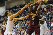 A.J. English #5 of the Iona Gaels grans a rebound and looks to pass as Micah Seaborn #10 and Josh James #0 of the Monmouth Hawks defend during the first half of a college basketball game at the MAC on February 19, 2016 in West Long Branch, New Jersey.