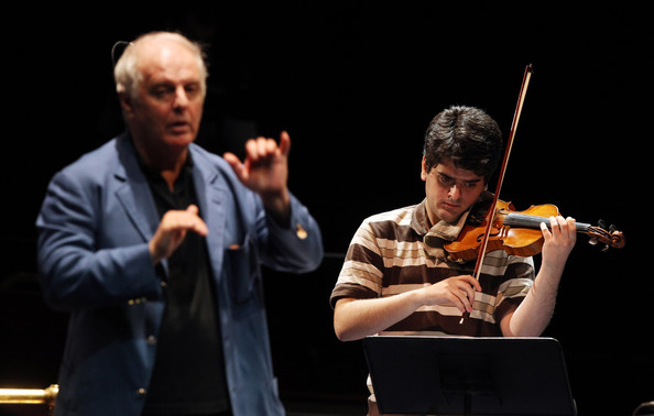 Daniel Barenboim Conductor Daniel Barenboim (L) directs his son Michael Barenboim during a rehearsal of The West-Eastern Divan youth orchestra in the Royal Albert Hall ahead of their performance in the BBC Proms tonight on August 21, 2009 in London, England. The orchestra was founded by Daniel Barenboim, an Argentine of Jewish descent and the late Palestinian-born Edward Said in 1999 and is based in Sevilla, Spain. The project involves young musicians from a variety of countries in the Middle East including Egypt, Iran, Israel, Jordan, Lebanon, Palestine and Syria. Although not described as a political project the orchestra serves as an example of Barenboim and Said's vision of understanding and collaboration between Israelis and Palestinians.
