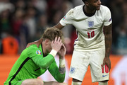 Jordan Pickford of England is consoled by team mate Raheem Sterling following defeat in the penalty shoot out after the UEFA Euro 2020 Championship Final between Italy and England at Wembley Stadium on July 11, 2021 in London, England.