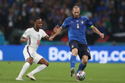 Giorgio Chiellini of Italy is challenged by Raheem Sterling of England during the UEFA Euro 2020 Championship Final between Italy and England at Wembley Stadium on July 11, 2021 in London, England.