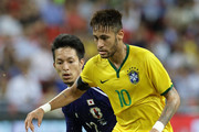 Neymar of Brazil (front) dribbles past Taishi Taguchi of Japan during the international friendly match between Japan and Brazil at the National Stadium on October 14, 2014 in Singapore.