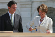 """House Majority Leader Eric Cantor (R-VA) (L) looks on as House Minority Leader Nancy Pelosi (D-CA) (R) tries to drive a nail during the """"First Nail"""" ceremony, signifying the start of construction of the 2013 Inaugural Platform on the West Front of the U.S. Captiol September 20, 2012 in Washington, DC. The winner of the November 6 presidential election will be sworn in on the platform on January 21, 2013."""