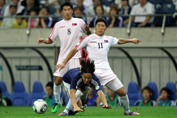 Jong Il-Gwan Shinji Okazaki (C) of Japan is challenged by Jong Il-Gwan of North Korea during the 2014 FIFA World Cup Brazil Asian 3rd Qualifier match between Japan and North Korea at Saitama Stadium on September 2, 2011 in Saitama, Japan.