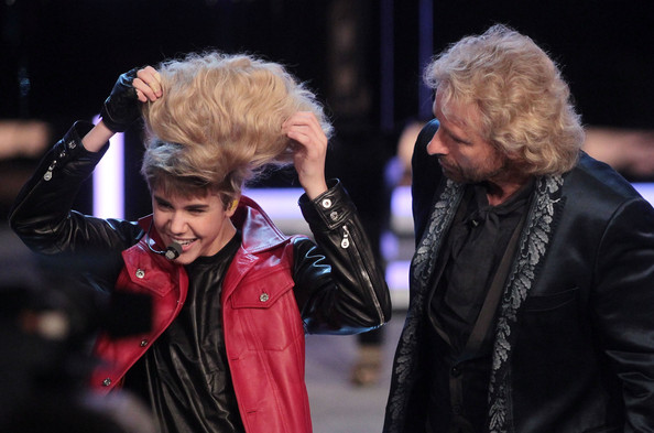 Justin Bieber TV-host Thomas Gottschalk (R) tries to put a blonde wig on Justin Bieber's head during the 'Wetten Dass ... ?' TV show at Augsburg fair ground on March 19, 2011 in Augsburg, Germany.