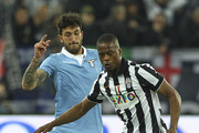 Patrice Evra (R) of Juventus FC is challenged by Danilo Cataldi (L) of SS Lazio during the Serie A match between Juventus FC and SS Lazio at Juventus Arena on April 18, 2015 in Turin, Italy.