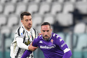 Franck Ribery of Fiorentina battles for possession with Aaron Ramsey of Juventus  during the Serie A match between Juventus and ACF Fiorentina at Allianz Stadium on December 22, 2020 in Turin, Italy. Sporting stadiums around Italy remain under strict restrictions due to the Coronavirus Pandemic as Government social distancing laws prohibit fans inside venues resulting in games being played behind closed doors.