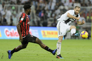 Giorgio Chiellini of Juventus passes the ball under pressure from Franck Kessie of AC Milan during the Italian Supercup match between Juventus and AC Milan at King Abdullah Sports City on January 16, 2019 in Jeddah, Saudi Arabia.