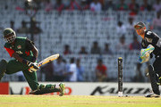 Collins Obuya of Kenya pulls the ball away towards the boundary, as Brendon McCullum of New Zealand looks on during the 2011 ICC World Cup Group A match between Kenya and New Zealand at M. A. Chidambaram Stadium on February 20, 2011 in Chennai, India.