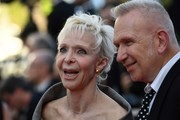 """French director Tonie Marshall (L) and French fashion designer Jean-Paul Gaultier pose as they arrive on May 15, 2016 for the screening of the film """"Mal de Pierres (From the Land of the Moon)"""" at the 69th Cannes Film Festival in Cannes, southern France.  / AFP / ANNE-CHRISTINE POUJOULAT"""